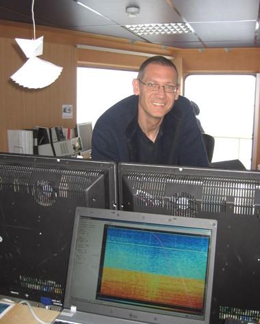 Dennis Anthony fra det Danske Farvandsvæsen arbejder med multibeamen. Til venstre ses en origamimodel, som illustrerer hvordan det flerstrålede ekkolod måler ned i vandet. Foto: Polarforskningssekretariatet