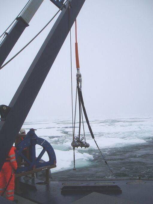 """Det seismiske udstyr på vej op af vandet. Øverst det orange kabel fra skibet ned til """"hovedet"""" hvorfra luftkanonen hænger og hydrofonkablet fortsætter agterud fra skibet"""