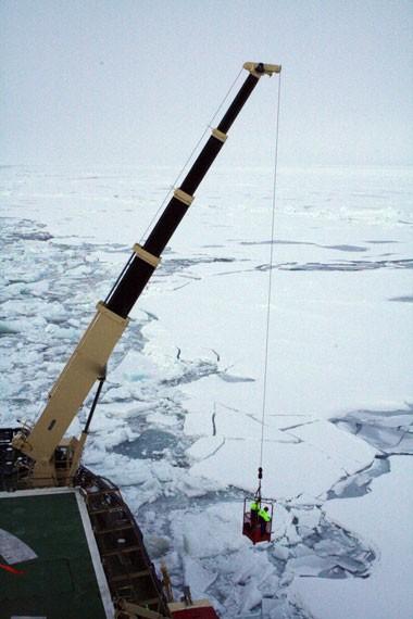 Forskerne bliver hejset ud på isen ved hjælp af en kran. Foto: Polarforskningssekretariatet.