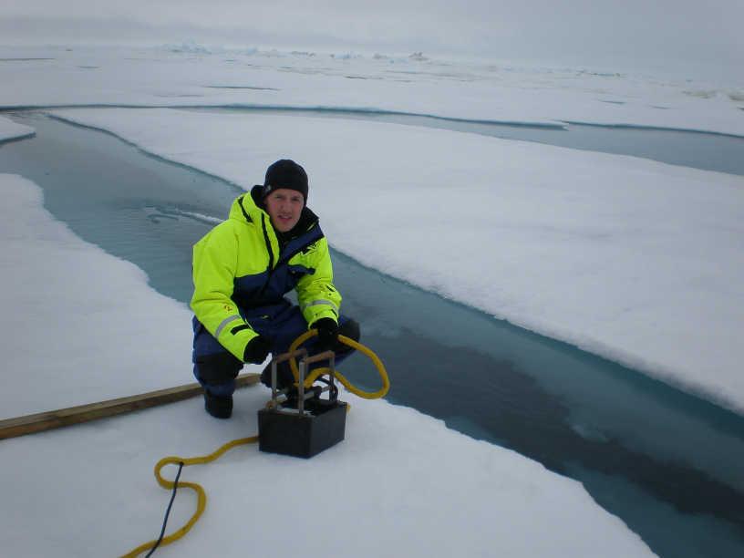 Niki Andersen med transducer ved kanten af en åben issprække.
