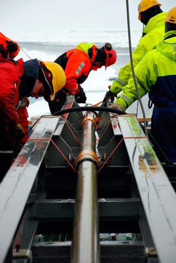 Røret med sedimentkernen hejses den over i en metalvugge. Foto: Daniella Gredin.