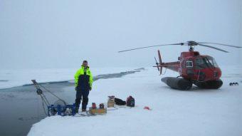 Steffen med det mobile CTD udstyr og helikopteren til hoejre Foto Leif Toudal Pedersen