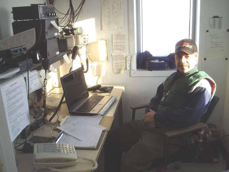 Dave Maloley i sin lille hule i Alert. Hulen er et lille kontor i Spinnaker bygningen. Her kommunikerer han med fly og med resten af verden. Foto: Trine Dahl-Jensen