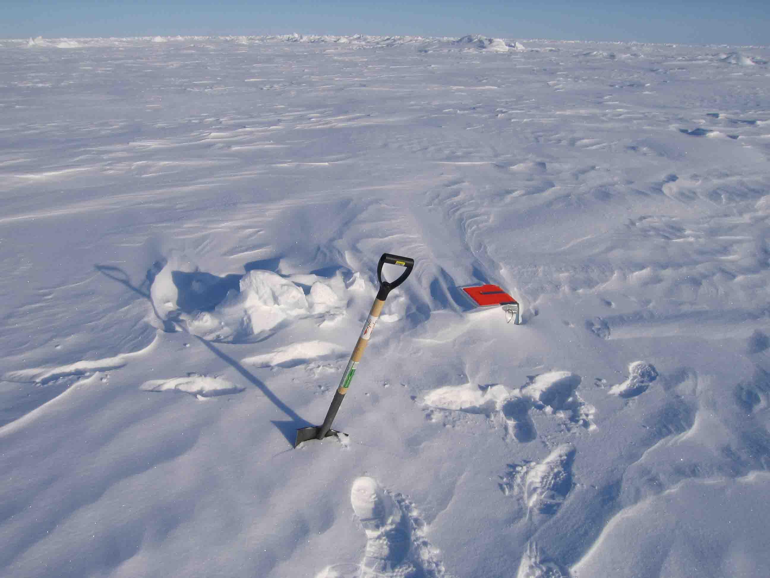 Receiver på isen næsten dækket af sne. Det er kun de orange låg på køletasken, der stikker op.