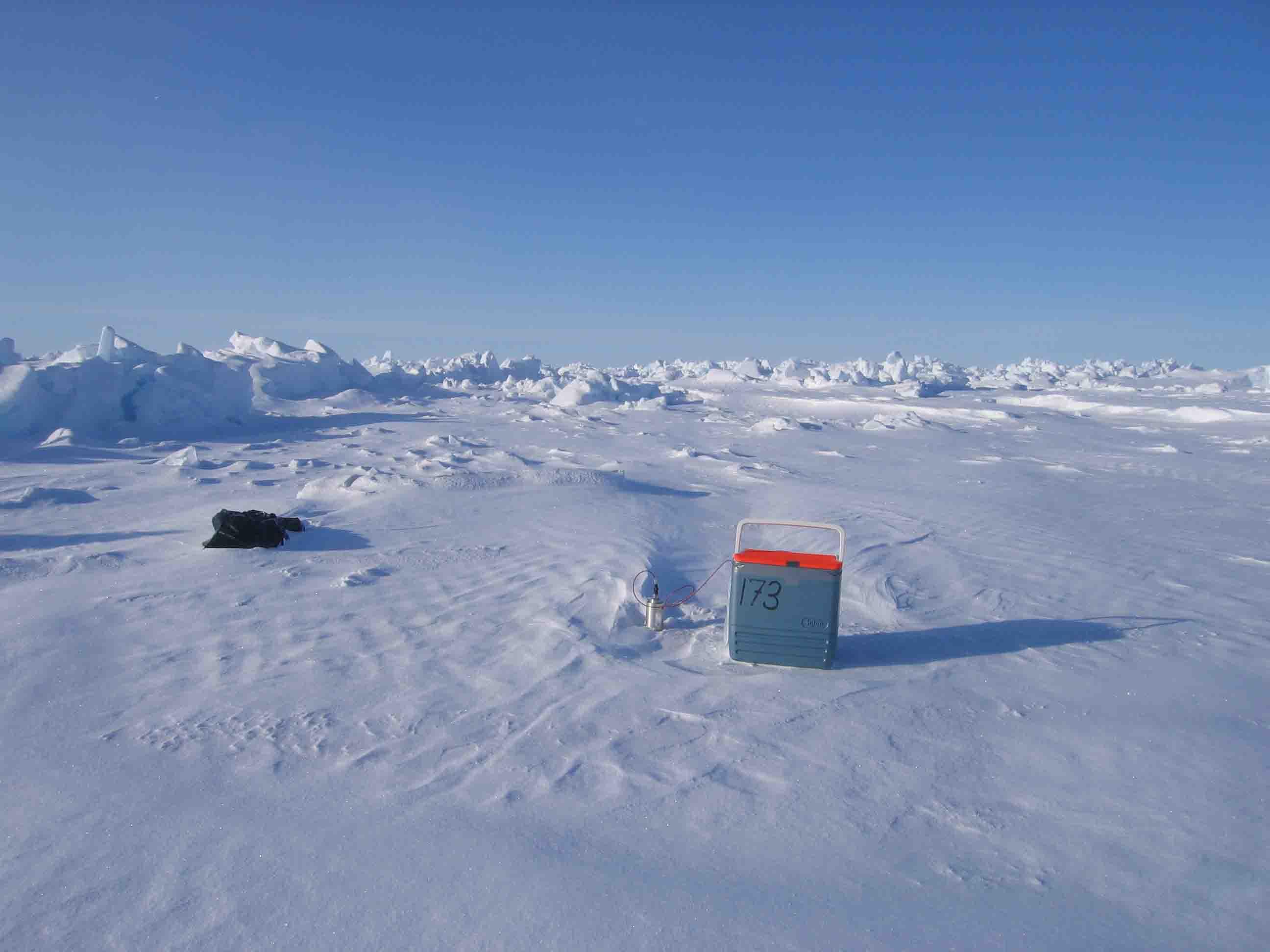Receiver på isen, der ikke er blevet dækket af sne. Under disse forhold er det let at finde instrumenterne. Køletasken holder batterier og datalogger varme. Tasken er forbundet med et seismometer, der står til venstre for tasken. Seismometeret opfanger bølgerne fra sprængningerne.