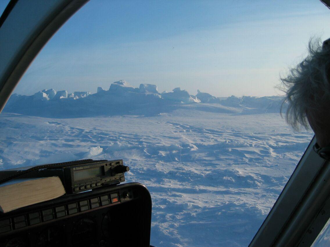 En typisk udsigt fra helikopteren under flyvning over havisen. Den store isryg i baggrunden er presset op, hvor tidligere isflager er stødt ind i hinanden.